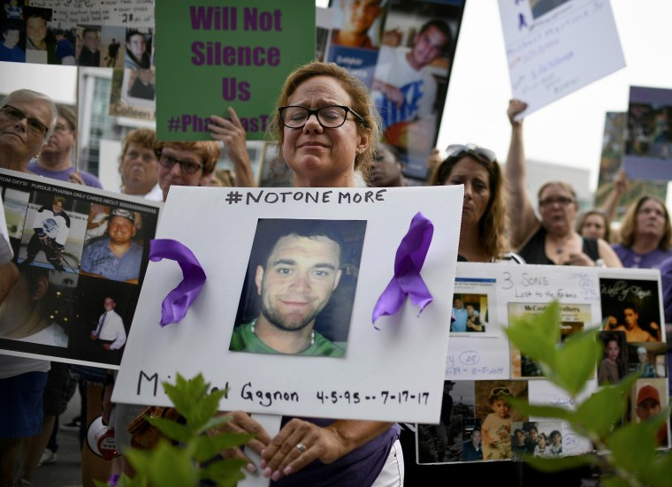 Image: Christine Gagnon holds a sign during a protest with others who have lost loved ones to OxyContin and opioid overdoses outside the Purdue Pharma headquarters in Connecticut on Aug. 17, 2018.