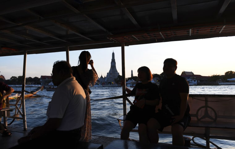 Image: Tourists take pictures of the Wat Arun Buddhist temple as they sail along the Chao Phraya river in Bangkok on Dec. 6, 2018.