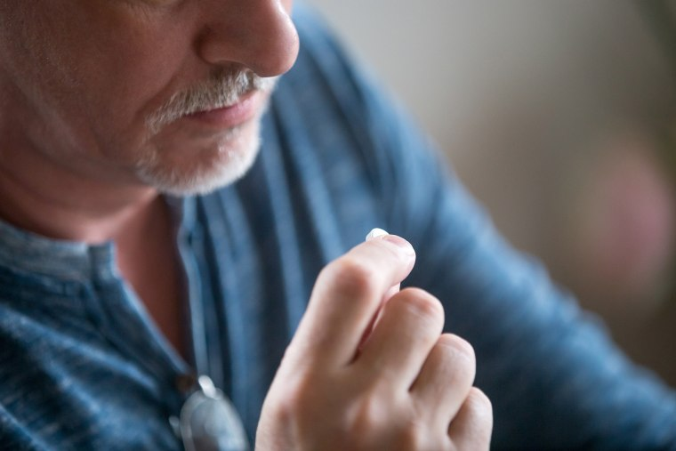 Image: Close up mature man holding in hand pill