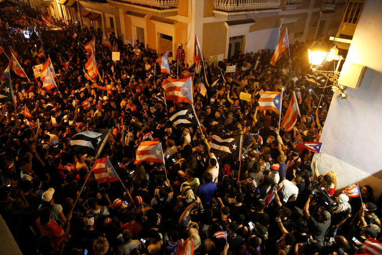 Image: Demonstrators chant slogans as they wave Puerto Rican flags during ongoing protests calling for the resignation of Governor Ricardo Rossello in San Juan