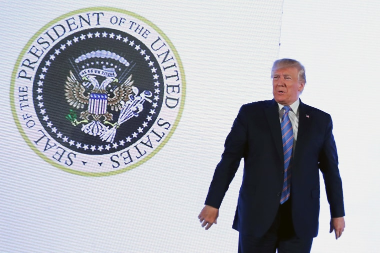 Image: U.S. President Trump stands next to altered presidential seal at Turning Point USA's Teen Student Action Summit in Washington