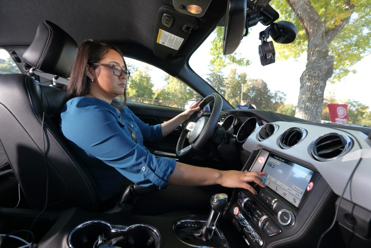 A woman drives a car with a smart display during the AAA car safety study.