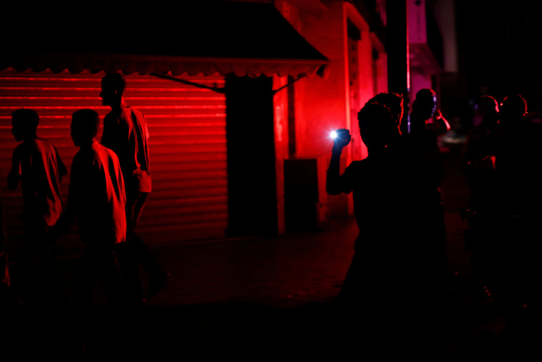 Image: People walk on the street during a blackout in Caracas
