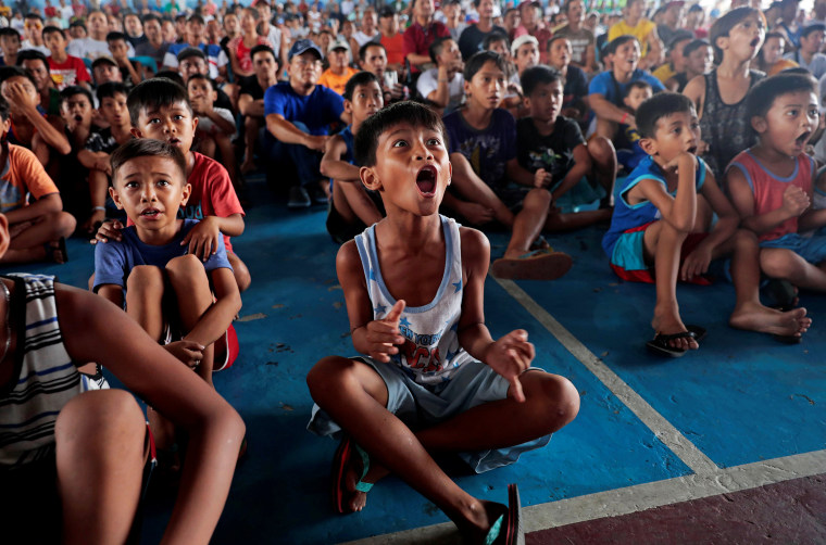 Image: Filipino boxing fans celebrate after Manny Pacquiao wins the WBA Welterweight fight against Keith Thurman of the U.S. during a live public viewing of the match in Marikina