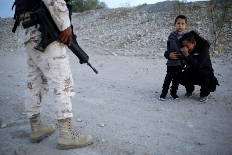 Image: Guatemalan migrant Lety Perez embraces her son Anthony while praying to ask a member of the Mexican National Guard to let them cross into the United States, as seen from Ciudad Juarez