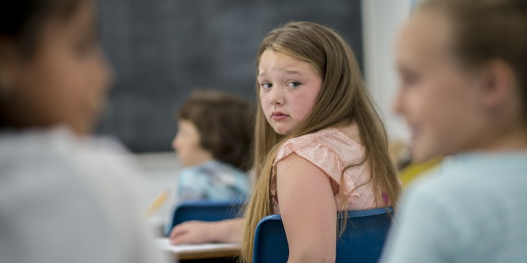 Young girl looks worried and hurt in classroom.
