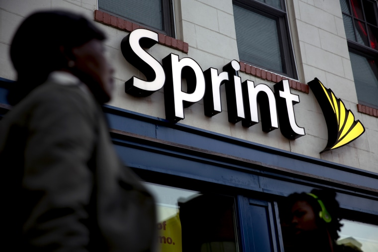 Image: Pedestrians walk past a Sprint store in Washington, D.C., in 2014.