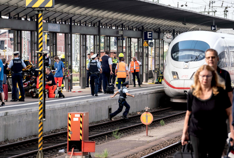 Image: Emergency services stand next to an ICE speed train at aFrankfurt's main station after a man pushed an 8-year-old boy and his mother in front of a train on July 29, 2019.