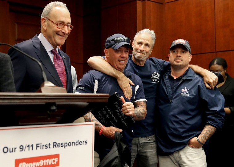 Image: Jon Stewart hugs 9/11 first responders with Sen. Chuck Schumer, D-NY, at a press conference after the Senate voted to renew the September 11th Victim Compensation Fund on July 23, 2019.