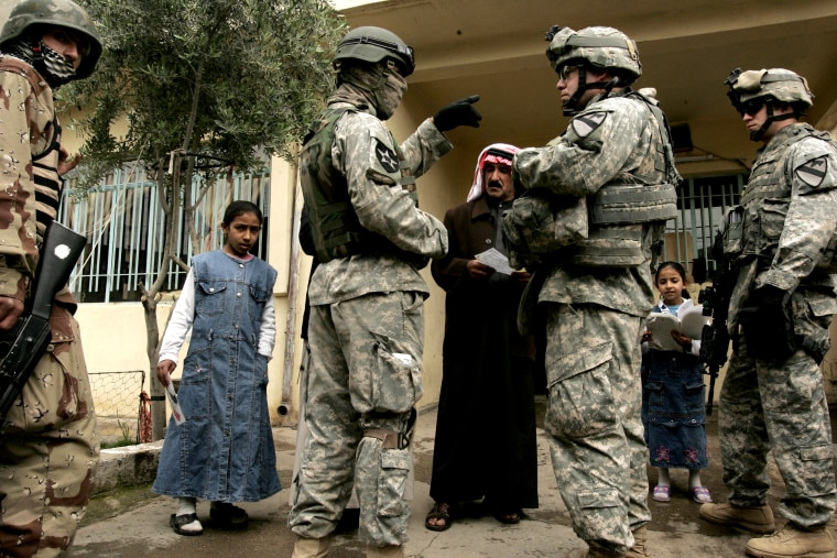 Image: An Iraqi man answers questions from U.S. soldiers with the help of an interpreter in Mosul in 2007.