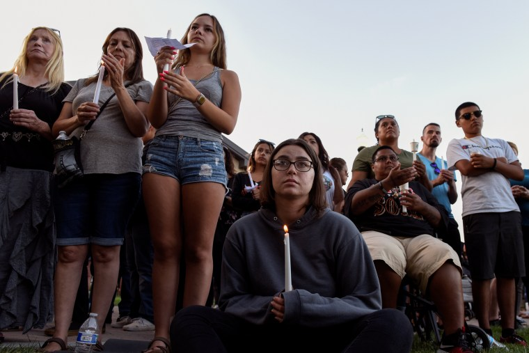 Image: Community members hold candles during a vigil outside of Gilroy City Hall for the victims of a mass shooting at the Gilroy Garlic Festival
