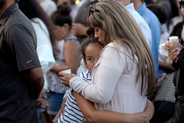 Image: Patty Lopez hugs her daughter Pricilla (9) during a vigil outside of Gilroy City Hall for the victims of a mass shooting at the Gilroy Garlic Festival