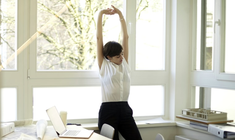 Image: Woman doing stretching exercise in her office