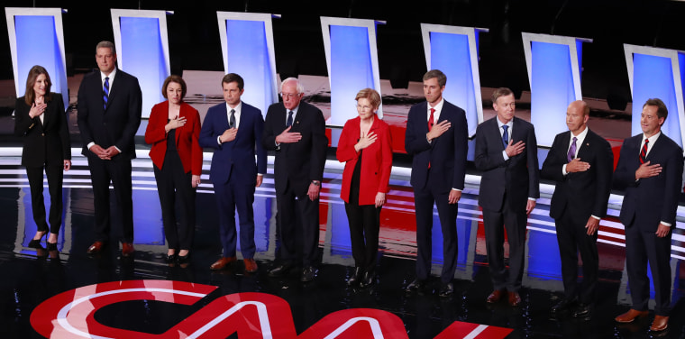 Image: The candidates stand during the national anthem on the first night of the second 2020 Democratic U.S. presidential debate in Detroit