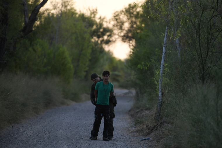 Image: A U.S. Border Patrol agent apprehends a migrant who illegally crossed the Rio Grande and attempted to avoid capture near Mission