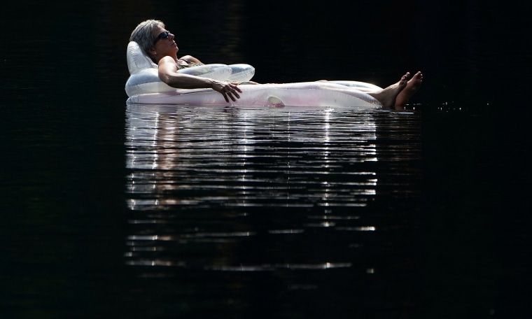 Image: A woman floats on an air mattress in Mazinaw Lake at Bon Echo park in Cloyne