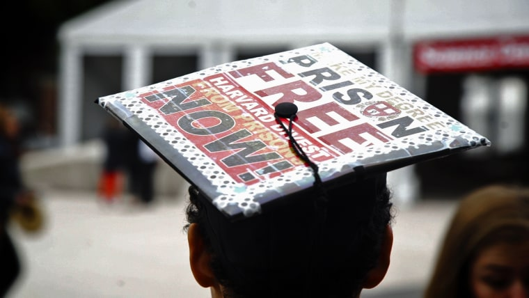 """Anneke Dunbar-Gronke wears a graduation cap outfitted with a sign that reads """"Make my degree prison free Harvard divest from prisons now!"""""""