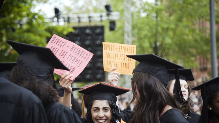 """In a show of protest, Harvard graduates hold up red and orange signs that say, """"Divest - reinvest free the people free the land"""" while university president Larry Bacow speaks."""