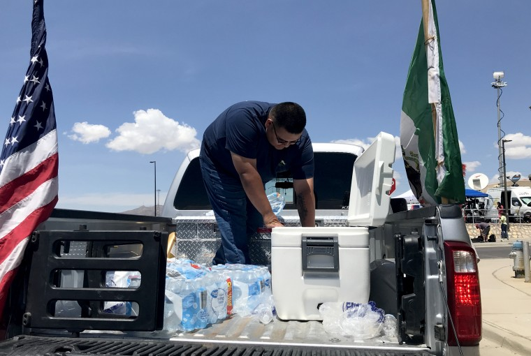 Image: Gabriel Gonzalez, 21, hands out bottles of water and soda near the Walmart.