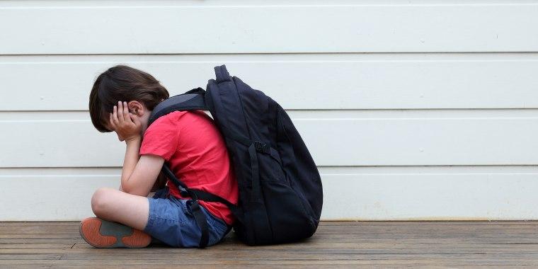 Sad boy in school hallway wearing backpack