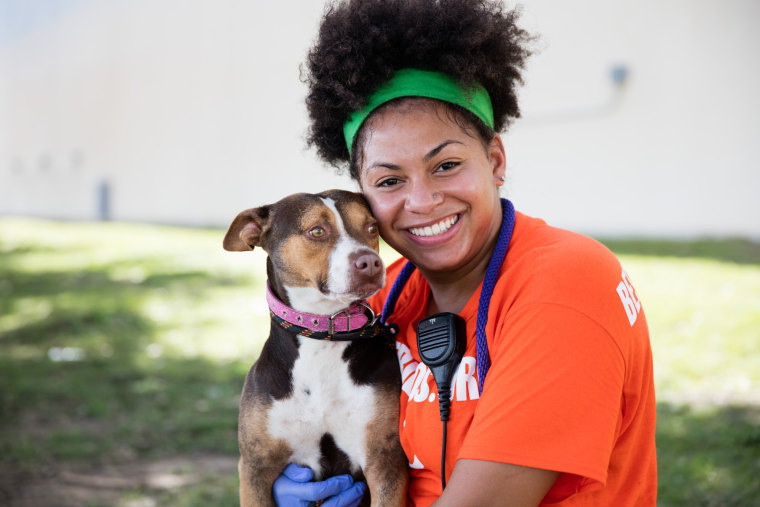 A Best Friends Animal Society volunteer hugs a rescue dog.