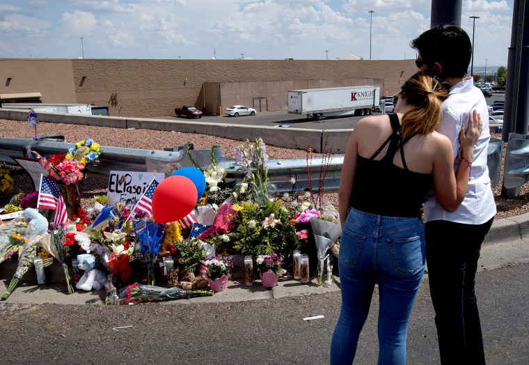 Image: Mourners hug next to a makeshift memorial outside the Cielo Vista Mall and Walmart a day after a mass shooting left 20 people dead in El Paso, Texas, on Aug. 4, 2019.