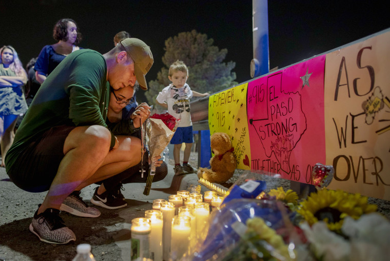 Image: Rene Aguilar and Jackie Flores mourn at a memorial for the victims of a mass shooting in El Paso, Texas, on Aug. 4, 2019.