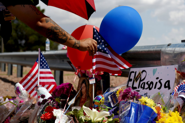 Image: A man places an American flag at a makeshift memorial near the site of a mass shooting that left 20 dead in El Paso, Texas, on Aug. 4, 2019.