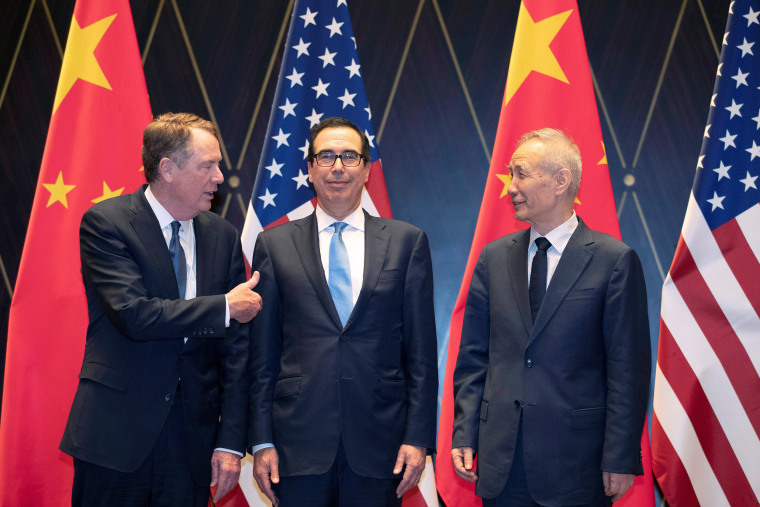 Image: Trade Representative Robert Lighthizer gestures towards Treasury Secretary Steven Mnuchin as he chats with Chinese Vice Premier Liu He before they pose for a family photo at the Xijiao Conference Center in Shanghai,
