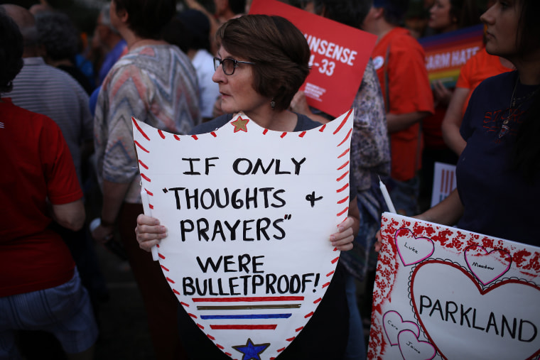 Image: Advocates of gun reform legislation hold a candle light vigil for victims of recent mass shootings outside the headquarters of the National Rifle Association