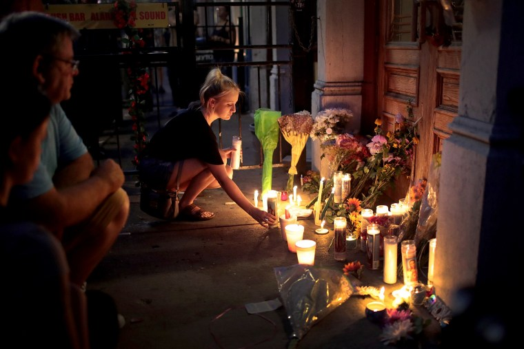 Image: Mourners leave flowers and candles at Ned Peppers Bar for the victims of a mass shooting on Aug. 4, 2019.