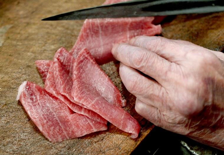 "A sushi chef cuts a fillet of high-quality fatty Atlantic bluefin tuna or \""o-toro\"" at a sushi restaurant in Tokyo"