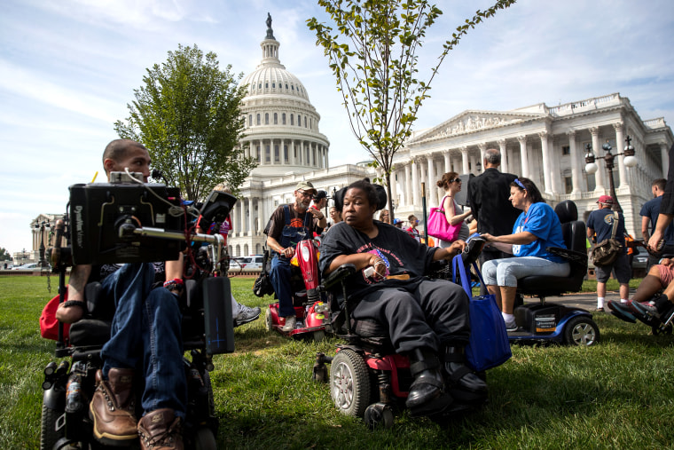 Image: Protesters wait for senators to arrive for a news conference on a health care bill which was part of an effort to repeal the Affordable Care Act in Washington on Sept. 26, 2017.