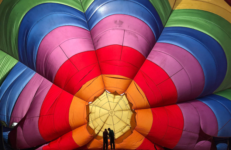 Image: Two crew members inspect a partially inflated balloon at the annual Bristol hot air balloon festival in Bristol, Britain