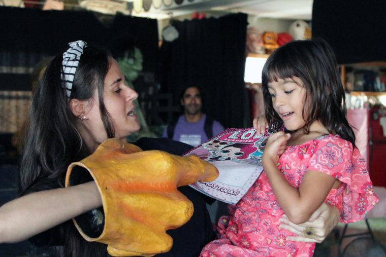 Yari Helfeld, co-director of Puerto Rican theater company Y No Habia Luz, reads a children's book to a girl in San Juan, Puerto Rico.