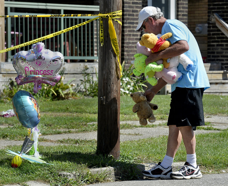 Image: Paul Laughlin leaves stuffed animals outside the scene of a house fire that left multiple people dead in Erie, Pennsylvania, on Aug. 11, 2019.