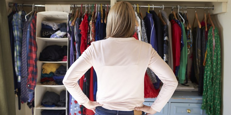 Woman looking at clothes in closet