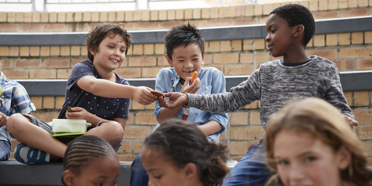 School children having lunch together outside the building