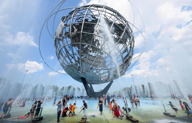 Image: People cool off at the Unisphere fountain at Flushing Meadow Corona Park in the Queens borough of New York during a heatwave on July 21, 2019.