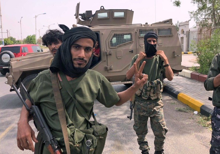 Image: Fighters of the UAE-trained Security Belt Force, dominated by backers of the the Southern Transitional Council (STC) which seeks independence for south Yemen, pose for a picture while standing before an armored vehicle in Khor Maksar in the center