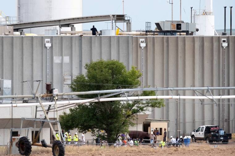 Image: Workers sit outside the Tyson Fresh Meats processing plant after a fire damaged the facility in Holcomb, Kansas, on Aug. 12, 2019.