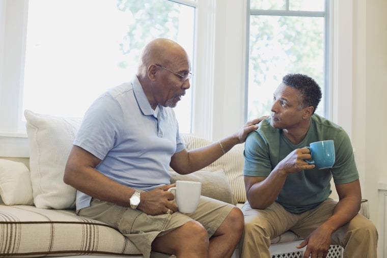 Image; Senior father and son talking while having coffee on sofa
