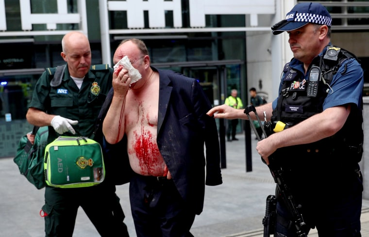 Image: An man with a facial injury and blood on his front is helped by a medic and police officer outside of the Home Office in London on Aug. 15, 2019.