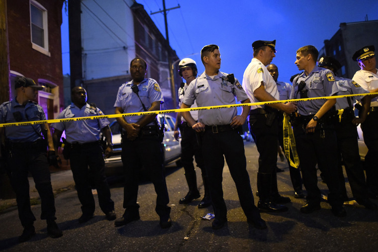 Police officers monitor activity near a residence while responding to a shooting in Philadelphia on Aug.14, 2019.