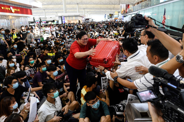 A tourist gives her luggage to security guards as she tries to enter the departures gate during a demonstration by pro-democracy protesters at Hong Kong's international airport on Aug. 13, 2019.