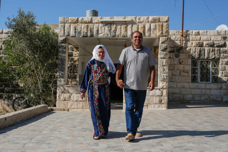Image: Muftia Tlaib, the maternal grandmother of Congresswoman Rashida, walk with her son Bassam outside their home in the village of Beit Ur al-Fauqa, in the occupied West Bank
