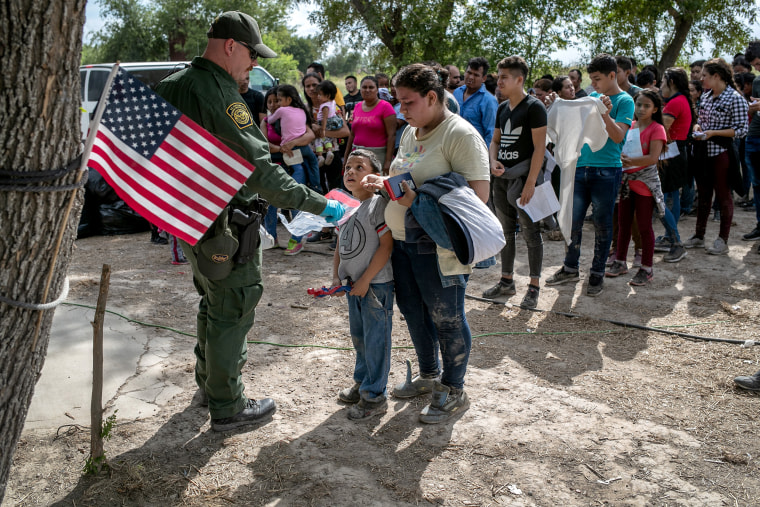 Image: A Border Patrol agent speaks to migrants before they were transferred to a McAllen, Texas, processing center in Los Ebanos on July 2, 2019.