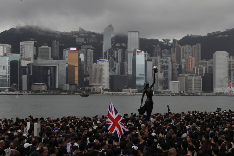 Image: Thousands of protesters carrying the British flag march near the harbor of Hong Kong.