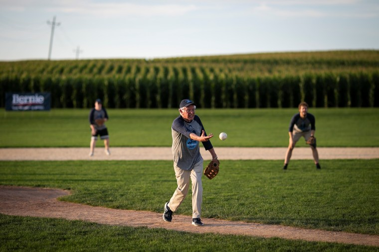 """Image: 2020 Democratic U.S. presidential candidate and U.S. Senator Bernie Sanders pitches during a baseball game between his staff, """"The Revolutionaries,"""" and the Leaders Believers Achievers Foundation at the """"Field of Dreams"""" movie site in Dyersville"""