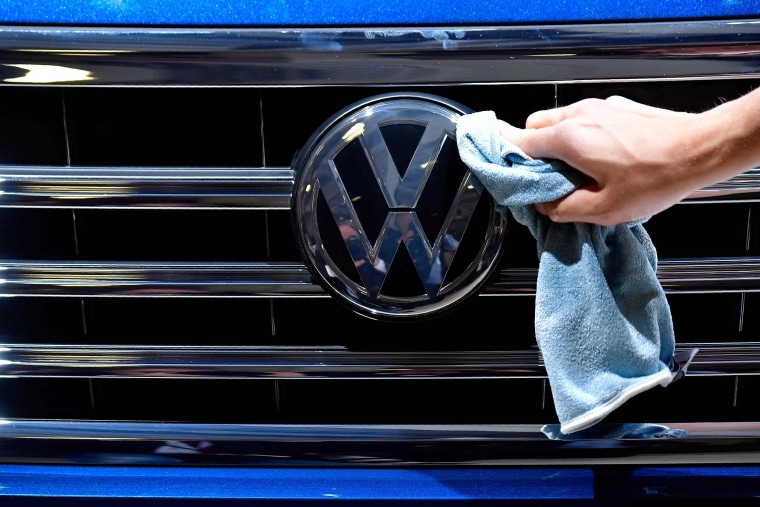 A staff member cleans the logo of a Wolkswagen ahead of the annual general meeting of the German carmaker in Berlin in 2018.